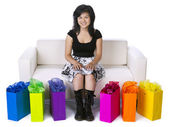 Attractive asian woman sitting on couch with shopping bags on si — Stock Photo