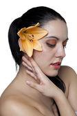 一个女人有一朵花的耳朵后面 — 图库照片