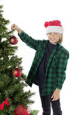 Adorable boy decorating tree — Stock Photo