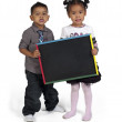Asian boy and girl holding chalkboard — Stock Photo