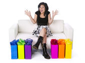Asian woman sitting on a couch with shopping bags on the side — Stock Photo