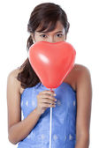 Attractive girl covering her face by red heart shape balloon — Stock Photo