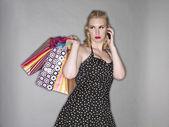 ショッピング バッグや携帯電話を持つ魅力的な女性 — ストック写真