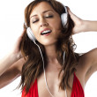 Attractive female listening music against white background — Stock Photo