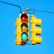 Yellow traffic / street lights on blue sky background - Stock Photo