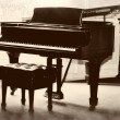 Vintage / retro piano and a seat in sepia — Stock Photo #13120163