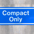Compact car only / warning, blue reflective metal sign post against gray cement wall - Stock Photo