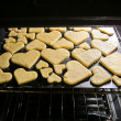 Baking fresh homemade home-made Valentine's heart love cookies lit in an oven — Stock Photo