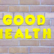 Bright yellow Good Health sign symbol title concept on brick wall care healthcare - Stock Photo