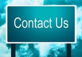 Background of a contact us sign guidepost and the sky — Stock Photo