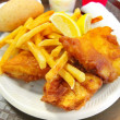 Delicious battered breaded fish on a plate with french fries, coleslaw salad and ketchup fish fry - Foto Stock
