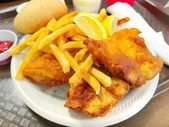 Delicious battered breaded fish on a plate with french fries, coleslaw salad and ketchup fish fry — Stock Photo