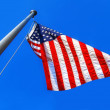 Stock Photo: US American blue, red and white stars and stripes patriotic flag isolated on blue sky background