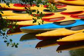 Colorful canoes and their reflection on water lake pond in a park — Stock Photo