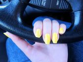 Female woman's driver's hand with yellow fingernails on the steering wheel — Stock Photo