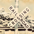 Railroad crossing sign and train gate in sepivintage retro old ancient aged — Stock Photo #42067119
