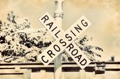 Railroad crossing sign and train gate in sepia vintage retro old ancient aged — Foto de Stock
