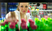 Young Woman reaching for a bottle — Stock Photo
