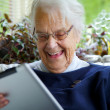 Stock Photo: Happy Elderly womusing tablet and laughing