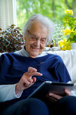 Happy Elderly woman using a tablet and laughing — Stock Photo