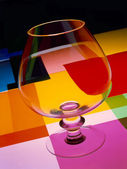 Glass of cognac with colors — Stock Photo