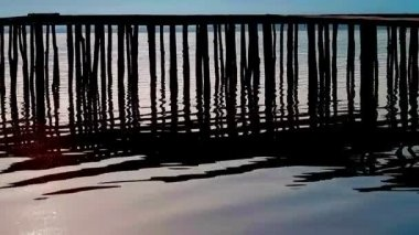 Rippling lake surface and silhouettes of wooden posts making pattern of vertical lines — Stock Video