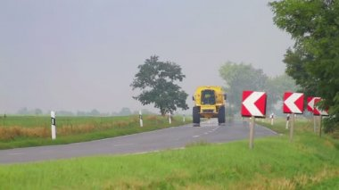 Agricultural vehicle passing on small road — Wideo stockowe