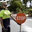 Road worker controls traffic with red stop sign — Stockfoto