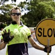 Road worker controls traffic with yellow slow sign - Stock Photo