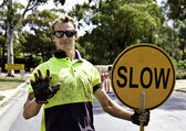 Road worker controls traffic with yellow slow sign — Stock Photo