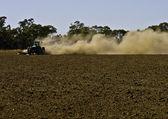 Agricoltore genera polvere come egli aratri campo — Foto Stock