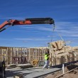 Workman guides roof trusses being lifted by crane onto new houses under construction — Stock Photo