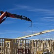 Crane lifts roof trusses onto new houses under construction — Stock Photo #26067571