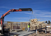 Workman guides roof trusses being lifted by crane onto new houses under construction — Foto Stock