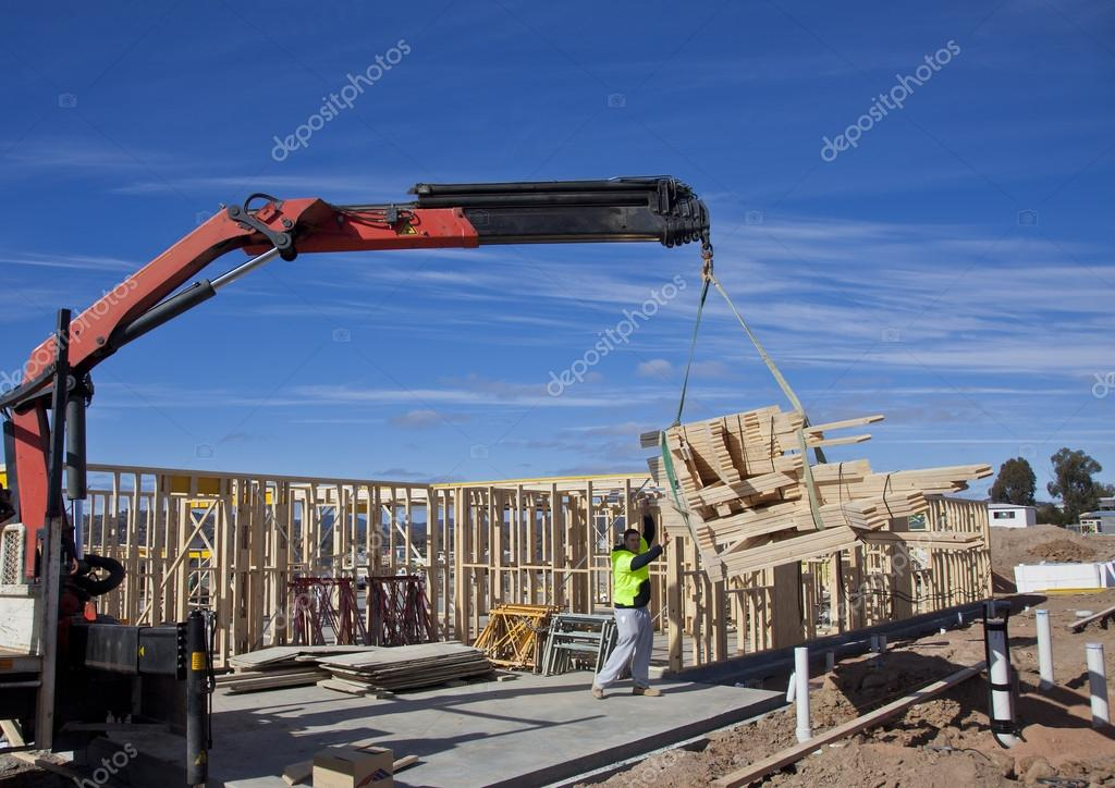 Workman guides roof trusses being lifted by crane onto new for 4 12 roof truss prices