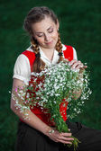 Girl student in park with flowers — Stock Photo