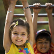 Children hanging on monkey bars — Stock Photo #39444857