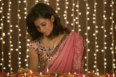 Woman lighting diyas — Stock Photo