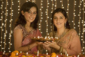Women holding a tray of diyas — Stock Photo