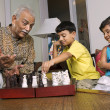 Stock Photo: Grandfather playing with grandchildren