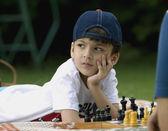 Menino jogando xadrez no piquenique — Foto Stock