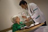 Doctor feeding his patient — Stock Photo