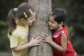 Girls hugging a tree — Stock Photo