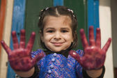 Girl with paint on her hands — Stock Photo