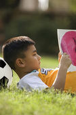 Boy lying with football under his head — ストック写真