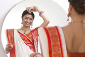 Bengali woman putting sindoor on forehead — Stockfoto