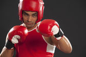 Indian boxer in gloves and head protector — Stock Photo