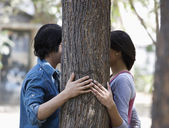 Couple with hands behind a tree — Stockfoto