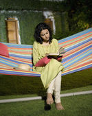 Woman reading a book in a hammock — Стоковое фото