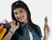 Woman holding shopping bags and a credit card — Stock Photo